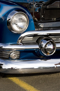 A closeup of the headlight and front bumper on a vintage car.