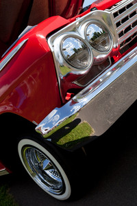 A closeup of the headlights and front bumper on a vintage American automobile.