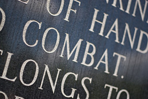 A closeup of the word COMBAT engraved on a war memorial plaque.  Shallow depth of field.