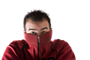 A cold man shivering and burying his face into his sweater. A great concept for HVAC.
