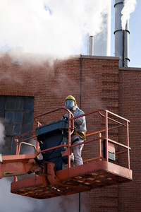 A commercial painter suited up with an industrial painting mask and suit white standing on a mechanical lift.