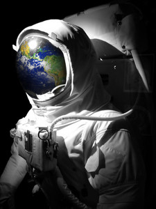 A complete astronaut space suit with a reflection of the earth reflecting in the helmet. Selective color. Earth photo courtesy of NASA.
