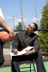 A confident coach speaking to one of his players on the basketball team.