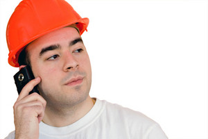A construction worker talking on a cell phone with copyspace.  Clipping path is included for easy isolation.