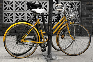A couple of bicycles chained to a post in the city. Selective color with highlight on the yellow.