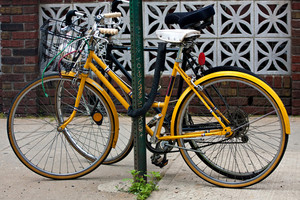 A couple of bicycles chained to a post in the city.