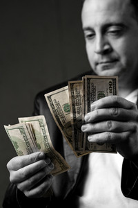 A crooked looking man counting a handful of one hundred dollar bills. Shallow depth of field.
