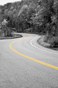 A curved New England road with selective isolated color and the center double lines in yellow.