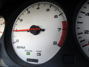A custom gauge cluster found in the interior of a sports car.  The dials are a white carbon fiber finish.