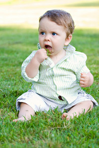 A cute baby boy about to eat a handful of green grass that he just grabbed.  He was stopped just before succeeding.