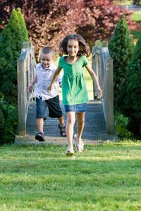 A cute little children running happily over a wooden bridge through the park.