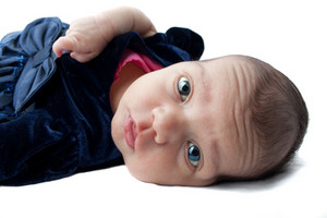 A cute newborn baby infant on a white backdrop.