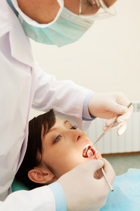 A dentist examining a girl's teeth