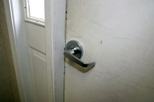 A door handle on a white door - the finish on the door is a little beat up.