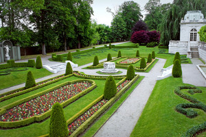 A fancy landscaped park or garden with flowers and highly groomed hedges.