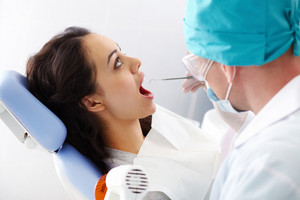A female patient sitting in the dental chair with her mouth open
