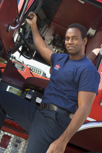 A firefighter standing by the cab of a fire engine