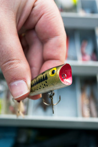 A fishermen selects the lure from his tackle box that he is going to use. Shallow depth of field.