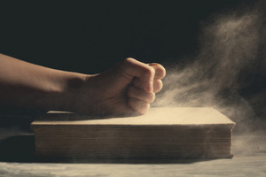A fist pounding down on an old book with dust flying around.