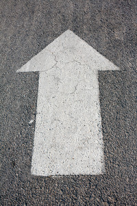A forwarded big white arrow on the road