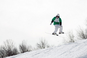 A freestyle skier catching some major air after launching off of a jump in reverse.