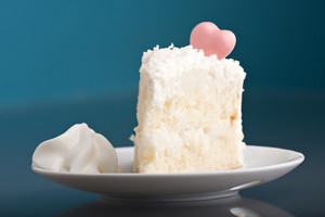 A fresh piece of coconut cream cake on a white plate with a bit of whipped cream on the side.