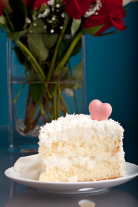 A fresh slice of coconut cake with a heart shaped candy on top.