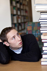 A frustrated student looks up at the high pile of textbooks he has to go through to do his homework assignment.