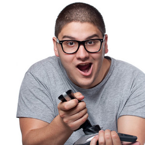 A fun loving video gamer playing with a wireless joystick over a white background.