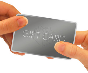 A gift card being exchanged through hands - isolated over a white background.  A clipping path is included.