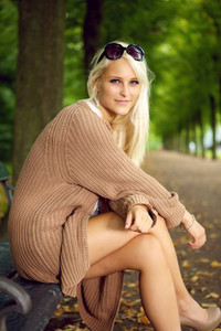 A glamorous young blonde fashion model sits on a park bench in a wool knee-length jersey and sunglasses.