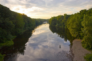 A glorious view of the Farmington River around dusk.  A patient fly fisherman is seen enjoying his hobby.