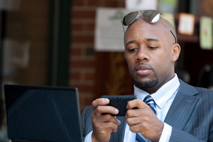 A good looking African American business man works on his laptop or netbook computer with a smart phone in his hands.