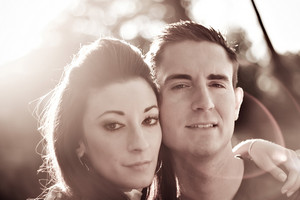 A good looking young couple posing together.  Backlit lighting with strong lens flare and sepia tone.