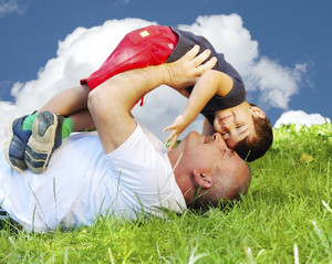 A grandfather and his kid laying and smiling on grass