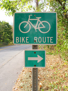 A green bike route sign on the side of the road