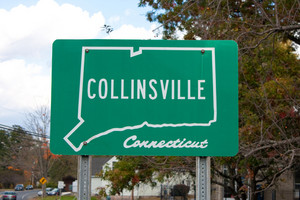A green public city street sign in Collinsville with the outline of the state of Connecticut in white.