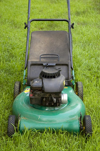 A green push style lawn mower ready for some weekend action.