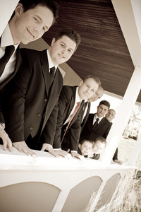 A groom and his groomsmen posing together in a row.