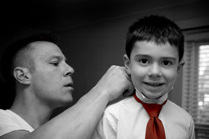 A groom helps his son get ready by putting on his tie.