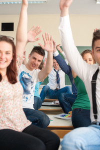 A group of cheerful students with their arms in the air sitting on tables in a classroom