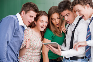 A group of five students looking at a tablet