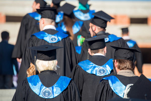A group of graduates with graduation hats from behind
