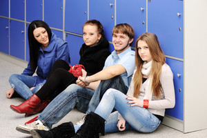 A group of high school students in the school hallway