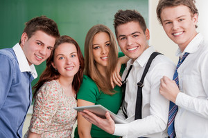 A group of smiling students posing in a classroom