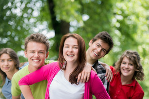 A group of smiling young people posing in woods