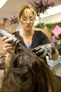 A hairdresser applying hair color to a clients head.  Shallow depth of field with focus on the hair.