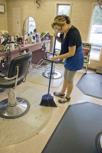 A hairdresser working in the salon sweeps up after her last client.