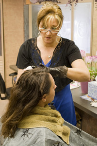 A hairdresser working on a clients hair color at the salon.