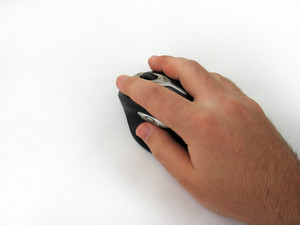 A hand guiding a modern wireless mouse - isolated over white.